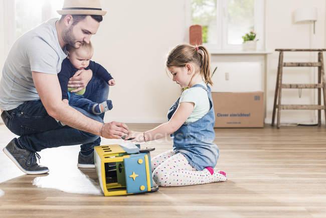 Vater mit zwei Kindern im neuen Zuhause spielen — Stockfoto