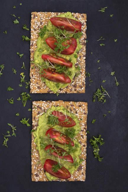 Crispbread з авокадо dip і помідорами — стокове фото