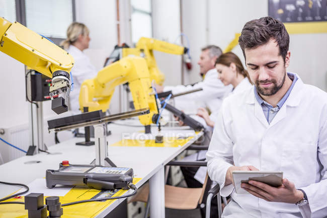 Engineer using tablet in factory with industrial robots — Stock Photo