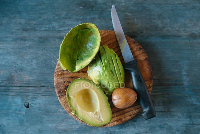 Noyau et le couteau sur la planche de bois — Photo de stock