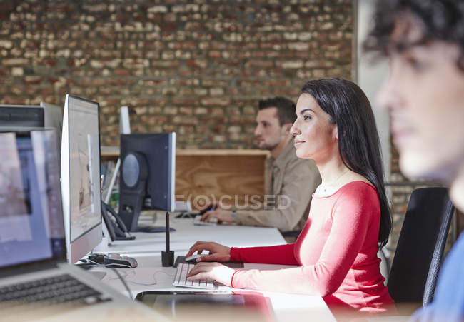 Woman working in office with colleagues — Stock Photo