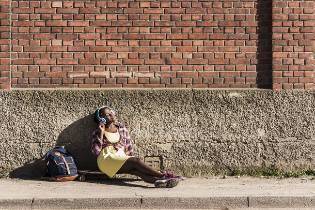 Woman sitting on ground and listening music — Stock Photo