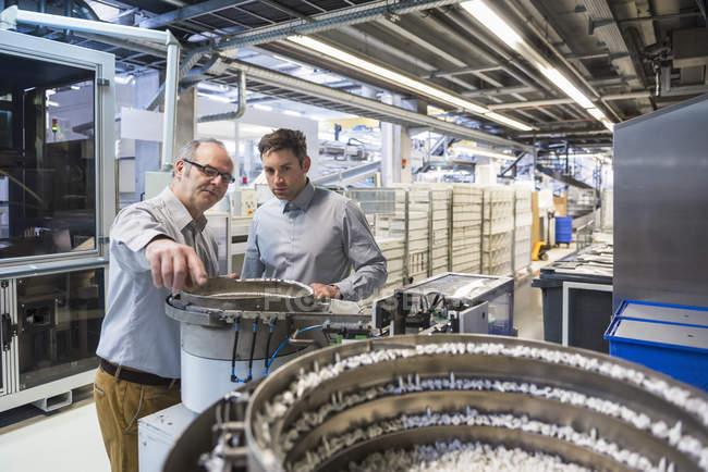Men examining outcome of machine — Stock Photo
