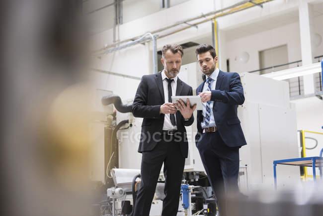 Businessmen sharing tablet — Stock Photo