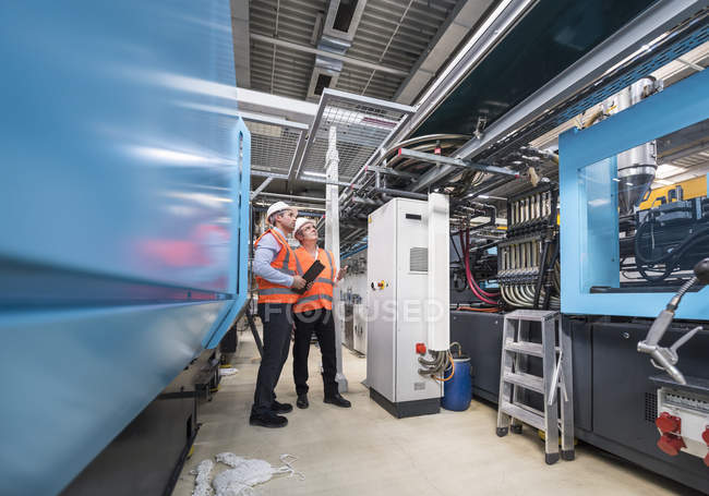 Men examining system in factory shop — Stock Photo