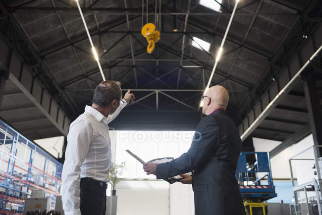Businessmen standing with clipboard at factory — Stock Photo
