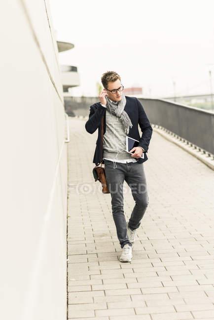 Businessman carrying digital tablet — Stock Photo
