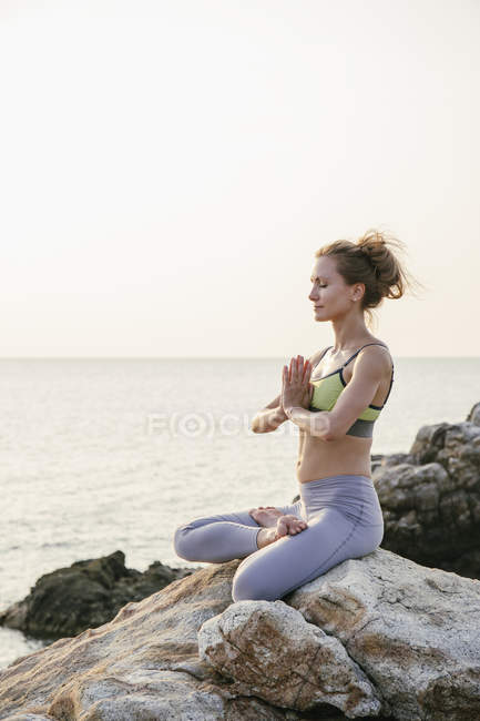 Woman meditating on beach — Stock Photo