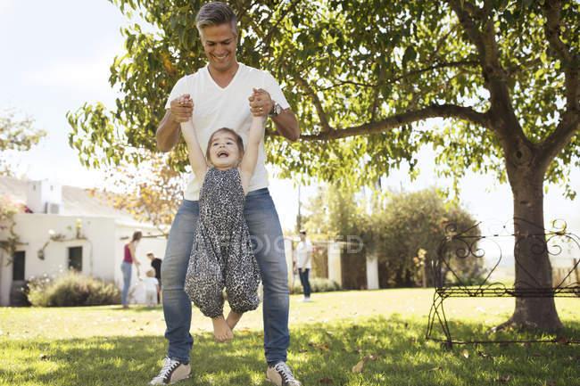 Père jouant avec sa fille dans l'herbe — Photo de stock