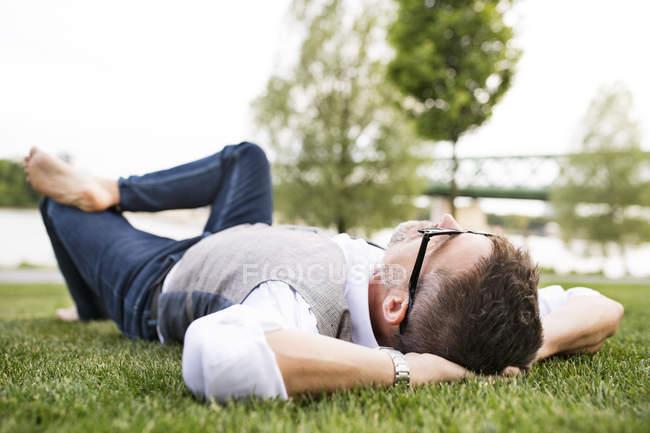 Empresário deitado na grama — Fotografia de Stock
