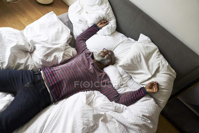Reifer Mann auf Bett liegend — Stockfoto