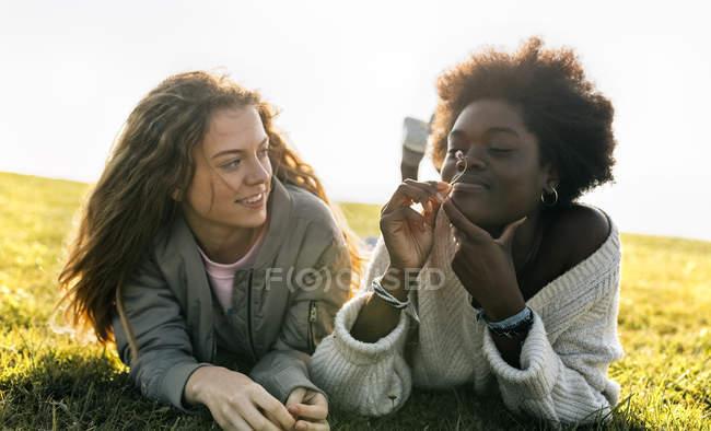 Freunde im Gras liegend — Stockfoto