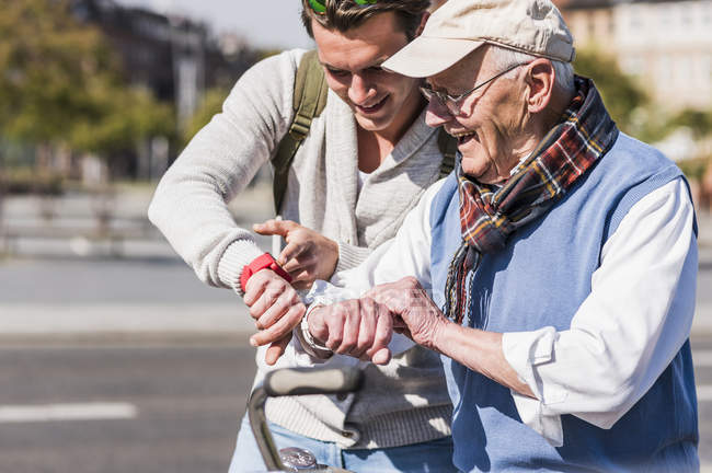 Человек и внук, глядя на часы — стоковое фото