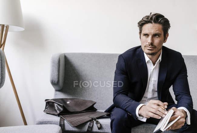 Бізнесмен з ноутбуком, сидячи на дивані — стокове фото