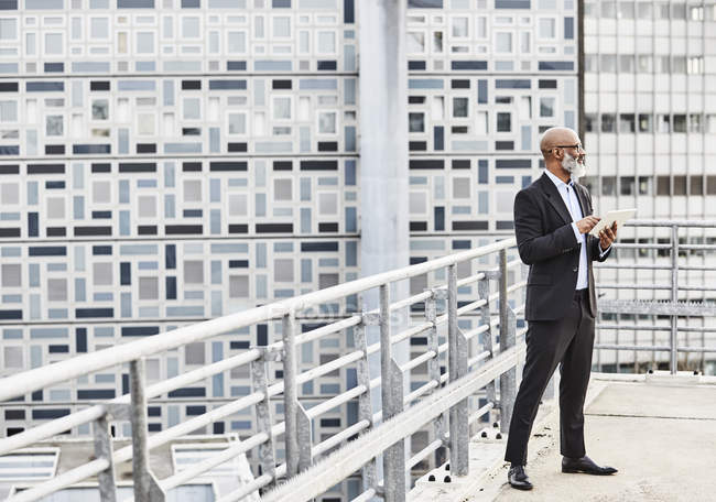 Businessman standing on office building — Stock Photo