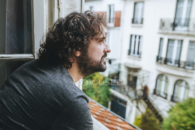 Man looking through opened window — Stock Photo