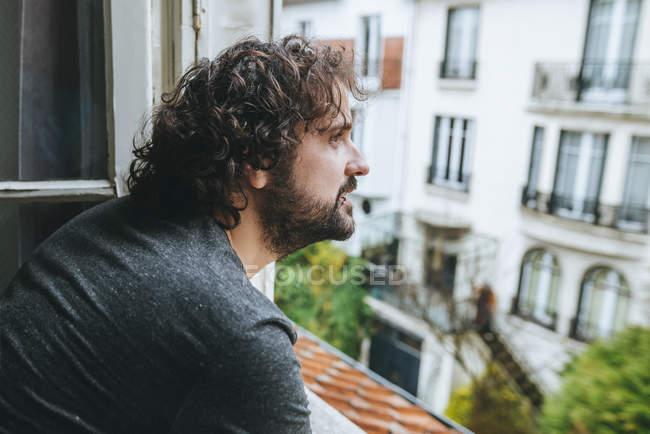 Человек смотрит через открытое окно — стоковое фото