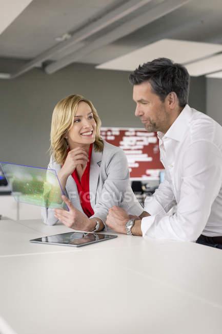 Бізнесмен і бізнес-леді за допомогою футуристичний переносний пристрій — стокове фото