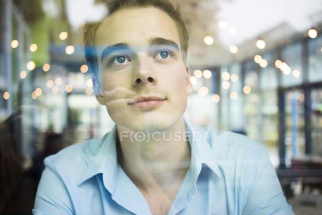 Mann sitzt hinter Fensterscheibe — Stockfoto
