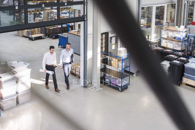 Businessmen walking in factory — Stock Photo