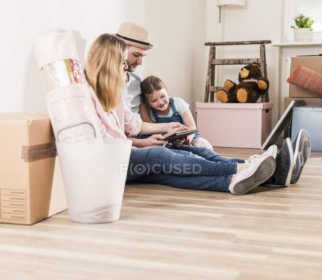 Parents and daughter using tablet in new home — Stock Photo