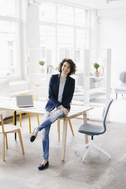 Geschäftsfrau sitzt auf Schreibtisch im Büro — Stockfoto