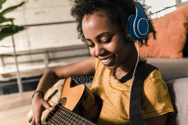 Woman with headphones playing guitar — Stock Photo
