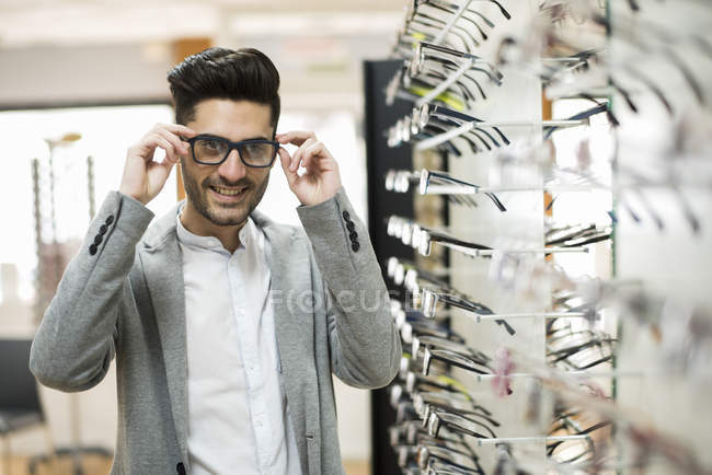 Man trying on glasses at optician shop — Stock Photo