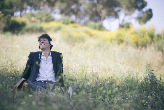 Young man in suit sitting on meadow listening to music — Stock Photo