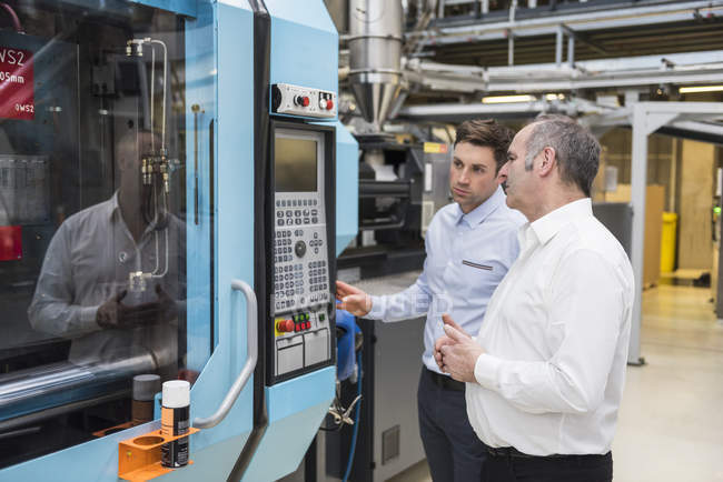 Two men looking at machine — Stock Photo