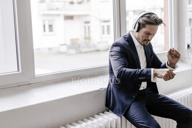 Businessman listening to music on headphones — Stock Photo