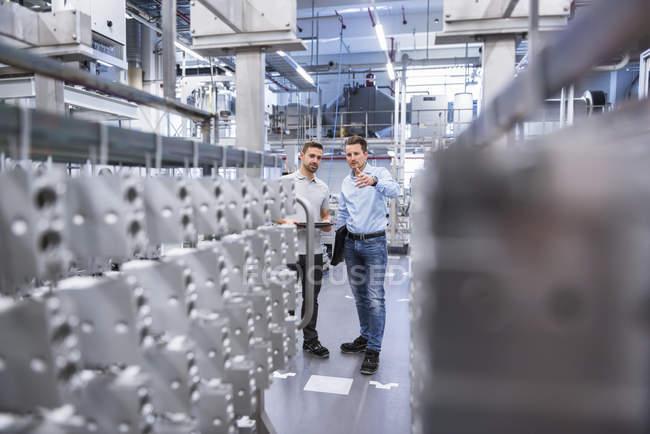 Men with tablet in factory shop floor — Stock Photo