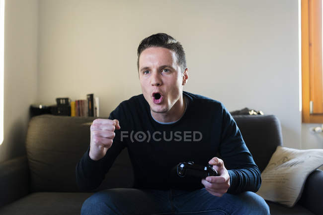 Screaming man sitting on the couch — Stock Photo