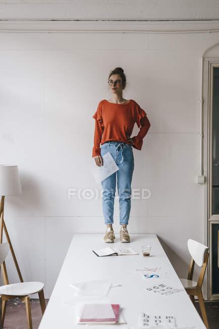 Femme debout sur la table avec des modèles de conception — Photo de stock