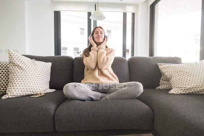 Женщина слушает музыку на диване — стоковое фото