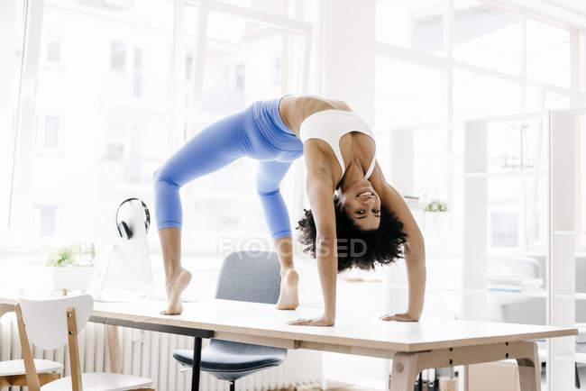 Woman doing backbend on desk — Stock Photo