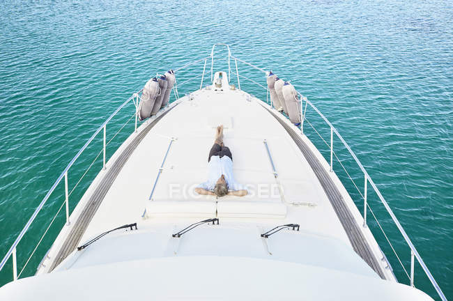 Man lying on deck of yacht — Stock Photo