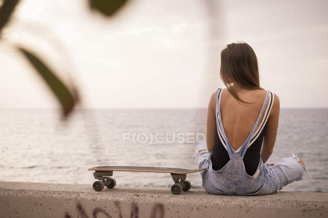 Woman with skateboard sitting on wall — Stock Photo