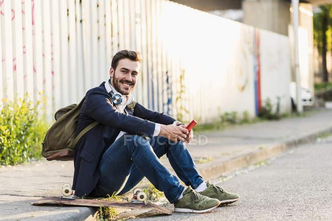 Человек сидит и держит мобильный телефон — стоковое фото