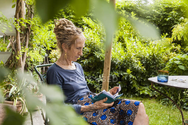 Senior woman with dreadlocks sitting in the garden looking at personal organizer — Stock Photo