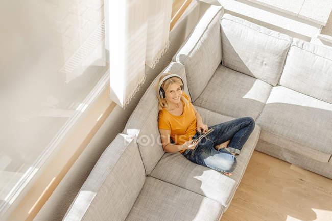 Mulher no sofá com fones de ouvido e tablet — Fotografia de Stock
