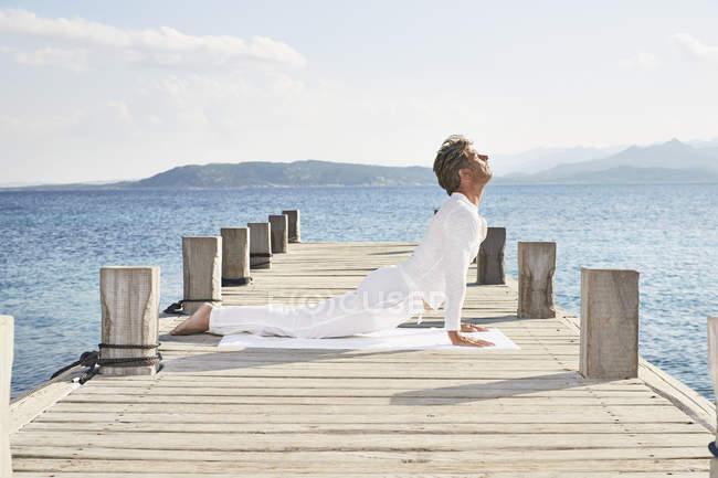Людина робить вправу йоги на пристані — стокове фото