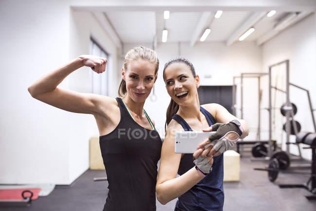 Female athletes taking selfies in gym — Stock Photo