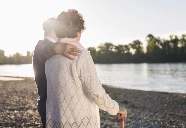 Пожилая пара, стоящая на берегу реки — стоковое фото