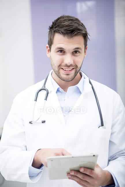 Médecin souriant utilisant le comprimé — Photo de stock