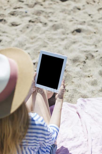 Donna seduta sulla spiaggia e utilizzando tablet — Foto stock