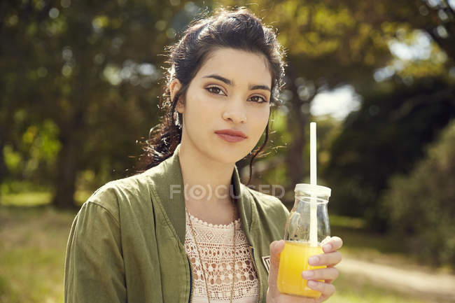 Молодая женщина со стаканом сока — стоковое фото