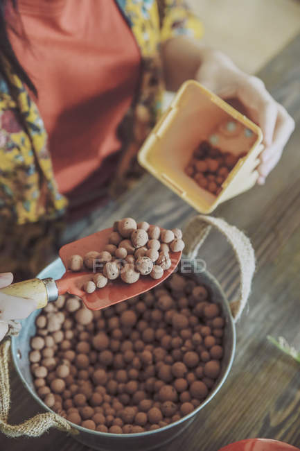 Female hands putting drainage soil in pot — Stock Photo
