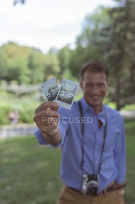 Людина холдингу миттєві фотографії — стокове фото