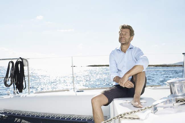 Hombre sentado en el barco de vela - foto de stock
